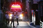 Автомобиль скорой помощи и сотрудники правоохранительных органов на месте происшествия в Токио. Архивное фото