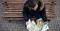 Молодой человек читает газету. Архивное фото