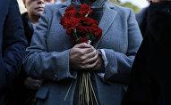 Женщина со цветами в руке. Архивное фото