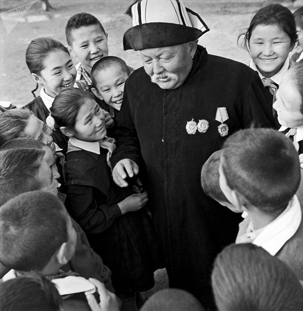 Народный артист Киргизской ССР Саякбай Каралаев — знаменитый сказитель эпоса Манас — в окружении детей из школы-интерната №3 (1965). Великий манасчи знал наизусть более полумиллиона строк из эпоса