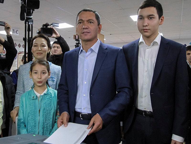 Кандидат в президенты Омурбек Бабанов, окруженный членами его семьи, бросает бюллетень на избирательном участке во время президентских выборов в Бишкеке