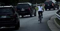 Велосипедиска рядом с кортежем президента США Дональда Трампа в Стерлинге, Виргиния. 28 октября 2017