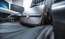 Кожаный портфель на офисном кресле. Архивное фото