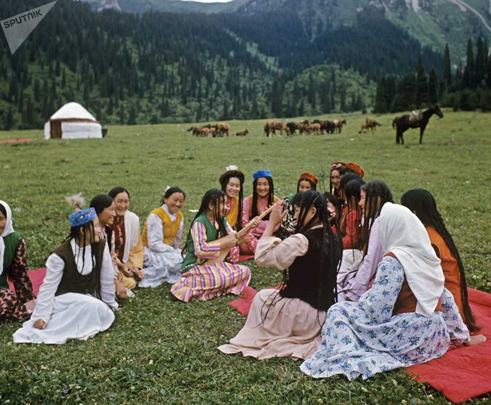 Юные кыргызки слушают комуз в ущелье Джеты-Огуз. Множество косичек на головах девушек означают, что они не замужем (замужние женщины заплетали одну или две косы).