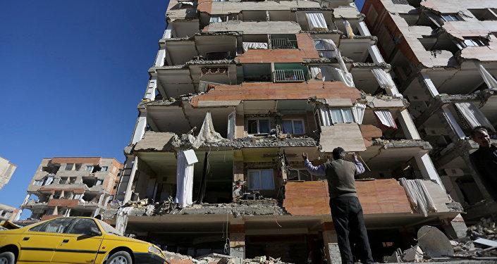Мужчина у разрушенного дома в результате землетрясения в иранской провинции Керманшах