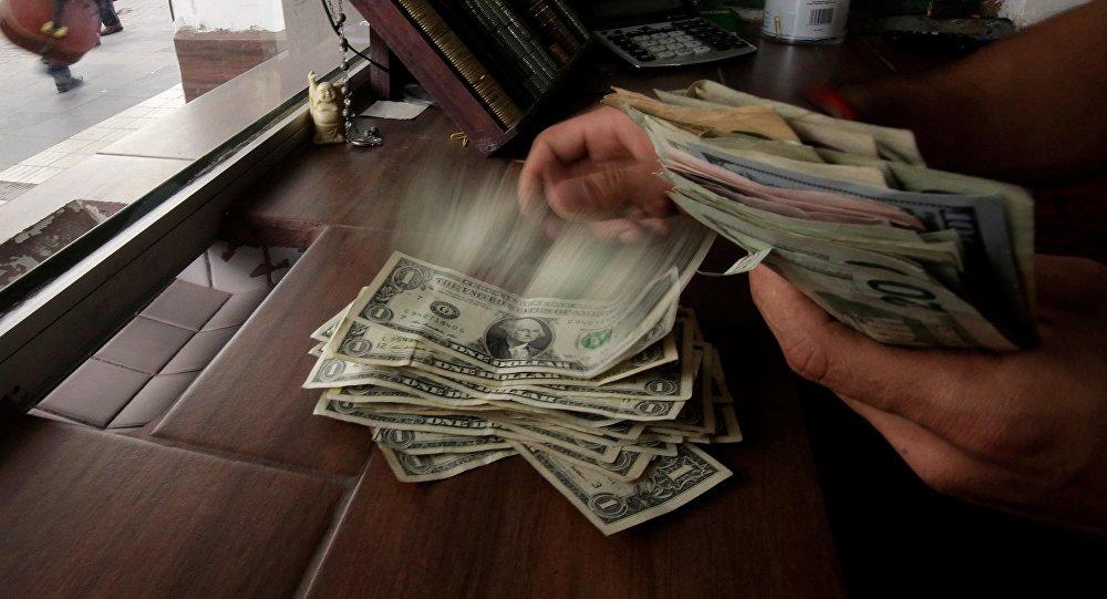 Сотрудник обмена валюты рассчитывает банкноты доллара США. Архивное фото