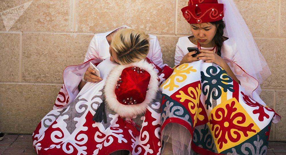 Девушки в национальных костюмах с телефонами. Архивное фото