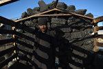 Рабочий выгружает уголь. Архивное фото