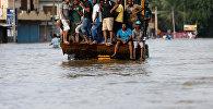 Люди на спасательной лодке в городе Биягама, Шри-Ланка.