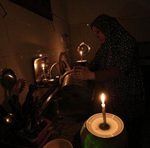 Женщина моет посуду при свечах в своем доме. Архивное фото