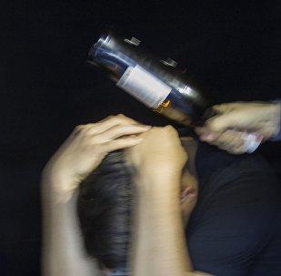 Мужчина бьет бутылке по голове другого. Иллюстративное фото