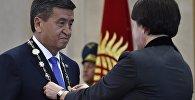 Председатель ЦИК Нуржан Шайлдабекова вручает знак президента КР Сооронбаю Жээнбекову на церемонии инаугурации в доме приемов Энесай Государственной резиденции Ала-Арча. 24 ноября 2017 года