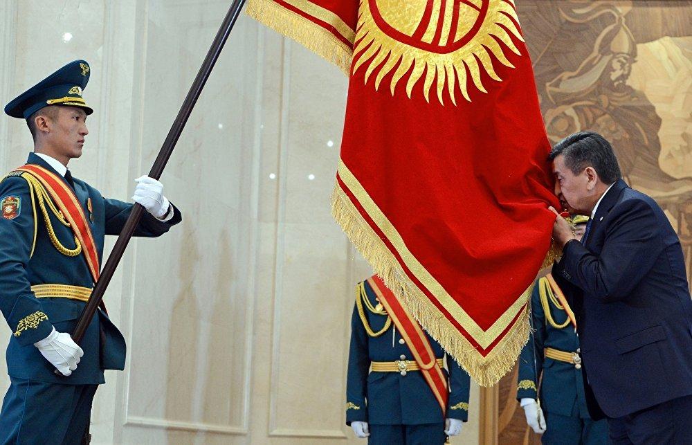 Президент Сооронбай Жээнбеков во время инаугурации целует флаг Кыргызстана