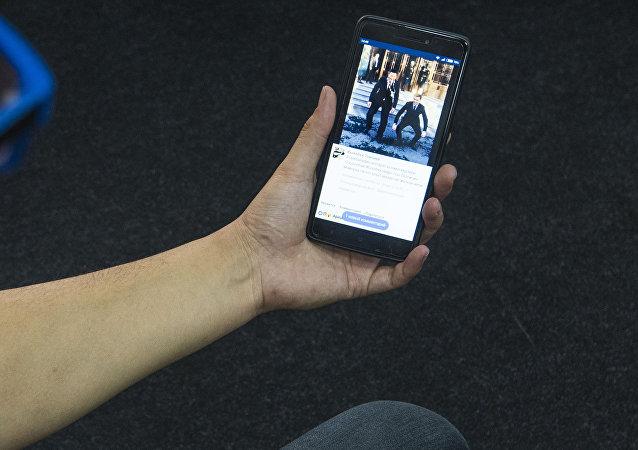 Парень смотрит на телефоне страницу Facebook, где неизвестный с нагрудным знаком президента Кыргызстана