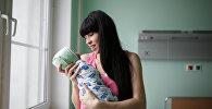 Мать с новорожденным ребенком в роддоме. Архивное фото