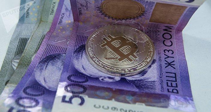 Сувенирная монета с логотипами криптовалюты биткоин с сомовыми купюрами. Архивное фото