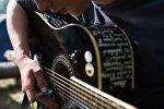 Гитара ойногон киши. Архивдик сүрөт
