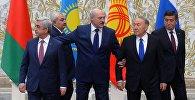 Белоруссиянын башчысы Александр Лукашенко жанында турган Нурсултан Назарбаевдин колунан тартып, сол жакка басуу керек дегендей белги берген