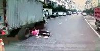 Женщина попала под колеса грузовика и чудом избежала смерти — видео из Китая