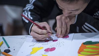 Мальчик с аутизмом рисует на бумаге. Архивное фото
