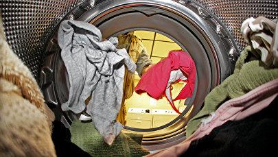 Мужчина кладет вещи в стиральную машину. Архивное фото