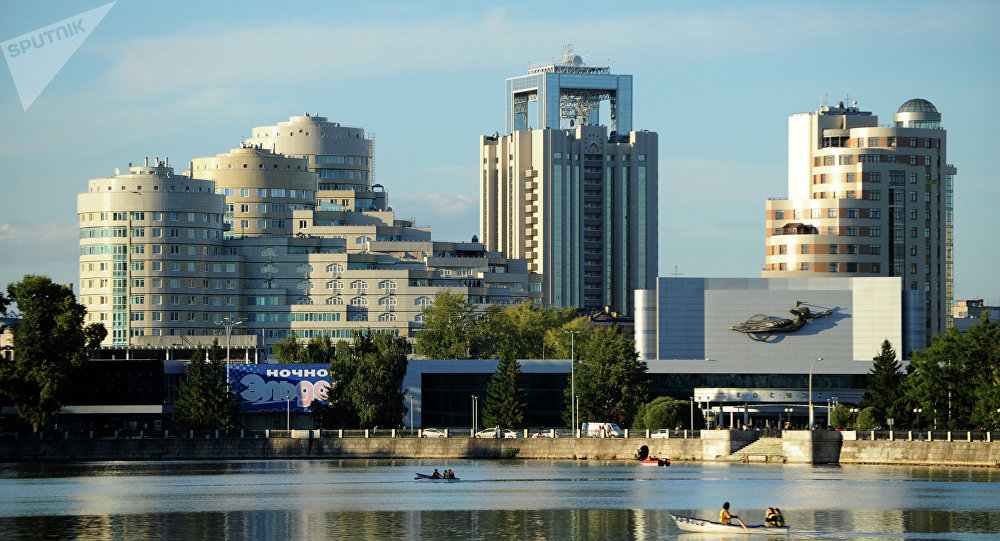 Вид на новостройки и кино-концертный театр Космос с набережной одного из городских прудов в Екатеринбурге