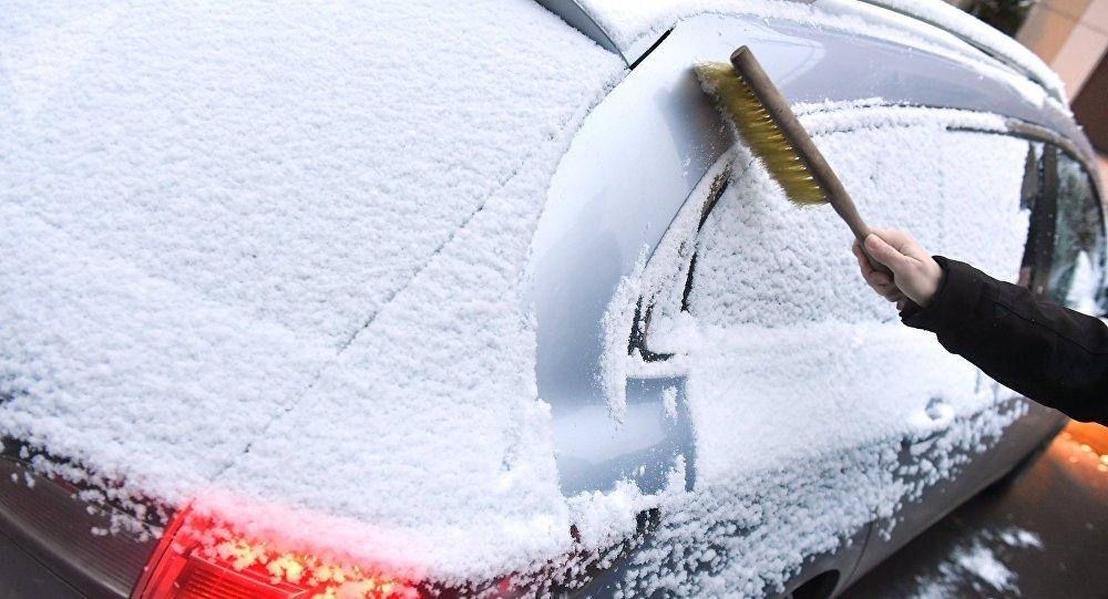 Мужчина чистит автомобиль после снегопада. Архивное фото