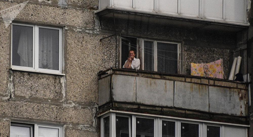 Архивное фото мужчины, который курит у себя на балконе