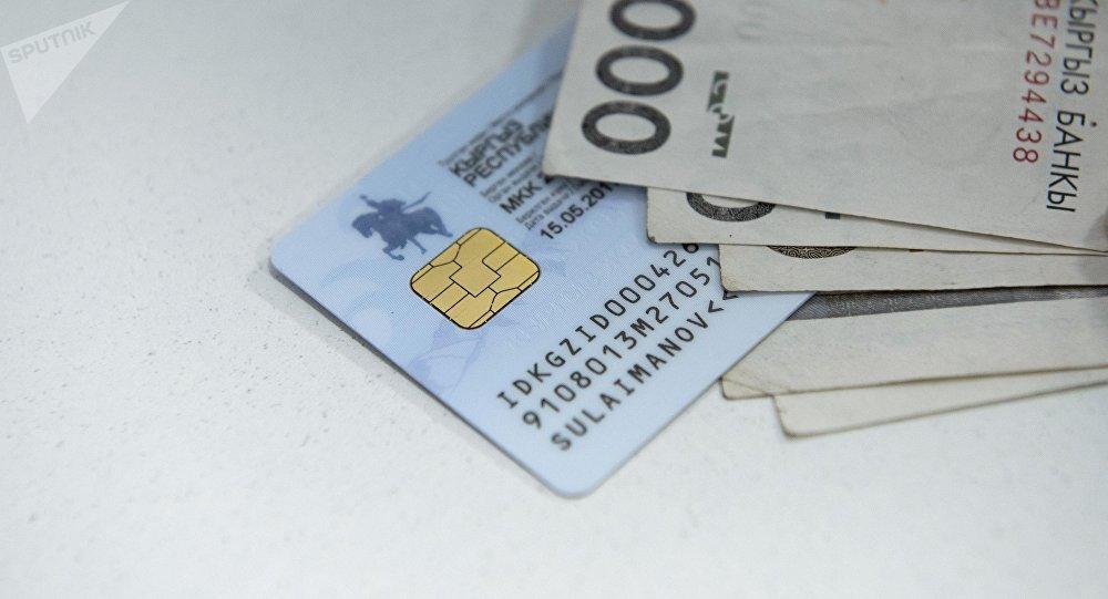 Новый биометрический паспорт гражданина Кыргызстана и деньги. Архивное фото