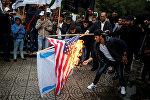Палестинские протестующие сжигают американский и израильский флаги в городе Газа. 6 декабря 2017 года