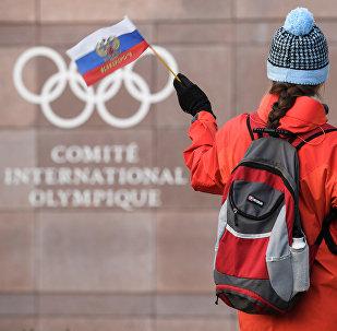 Сторонник размахивает российским флагом перед логотипом Международного олимпийского комитета (МОК) в штабе в Лозанне. Архивное фото