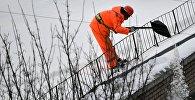 Сотрудник коммунальной службы сбрасывает снег с крыши жилого дома. Архивное фото