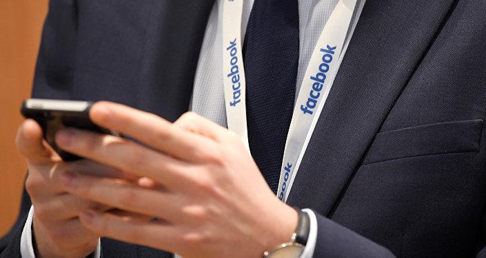 Человек с мобильным телефоном в штаб-квартире Facebook. Архивное фото