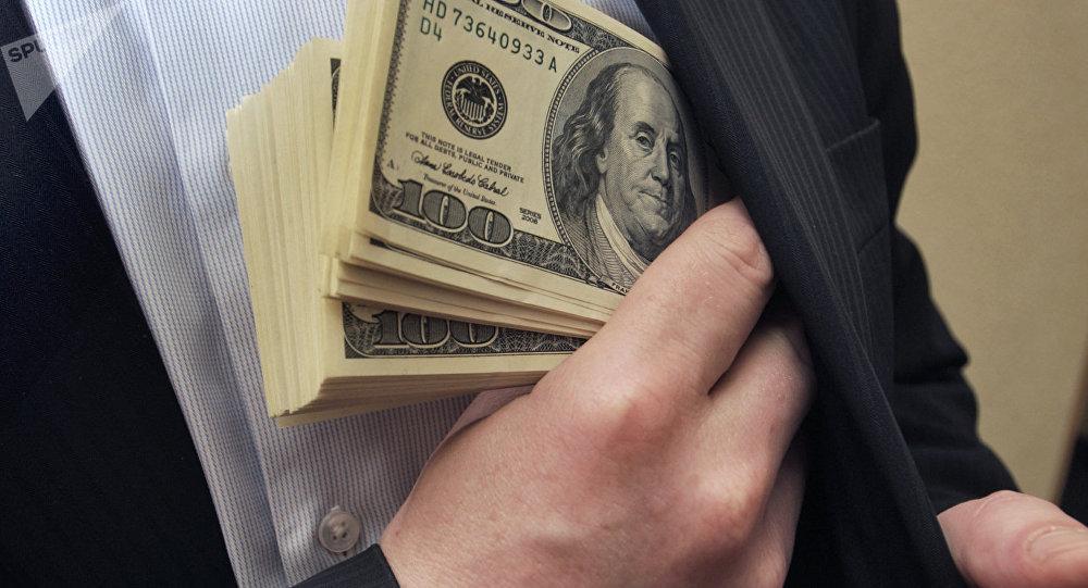 Мужчина кладет доллары в карман. Архивное фото