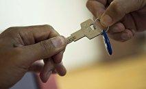 Ключи на фоне национальной валюты Кыргызстана. Архивное фото