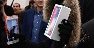 Покупатель демонстрирует новый смартфон. Архивное фото