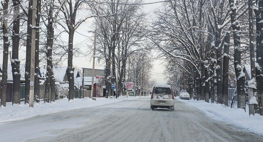 Автомобиль едет в одном из улиц Бишкека после снегопада. Архивдик сүрөт