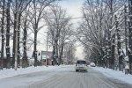 Автомобиль едет в одном из улиц Бишкека после снегопада. Архивное фото