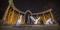 Горожане у памятника Курманжан-Датке в Бишкеке, украшенной по случаи нового года. Архивное фото