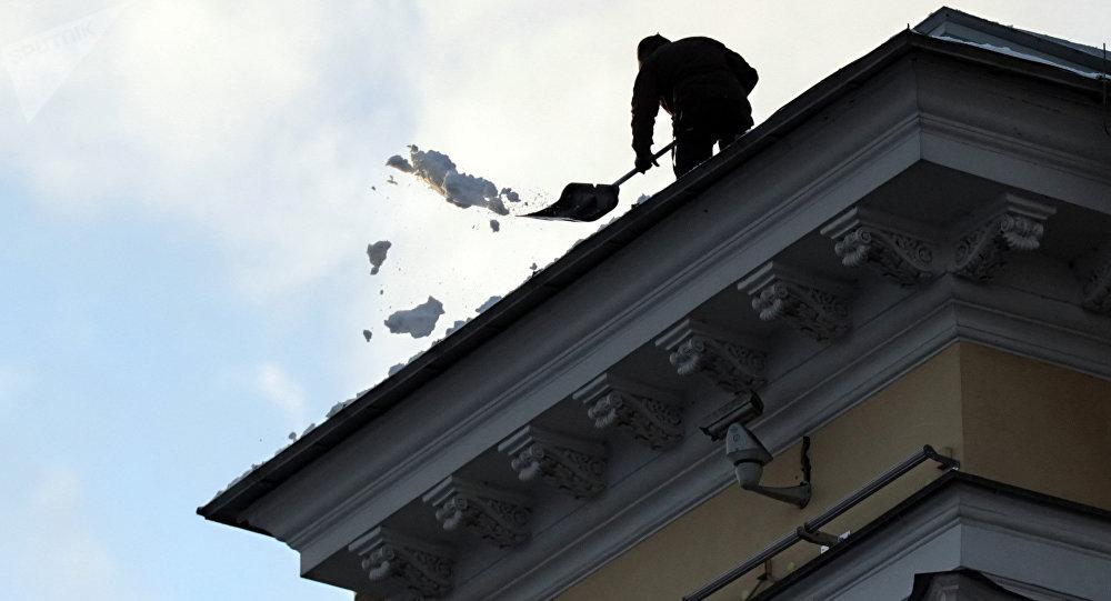 Дворник очищает от снега крышу здания. Архивное фото