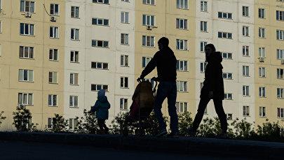 Мужчина и женщина с ребенком идут по тротуару. Архивное фото