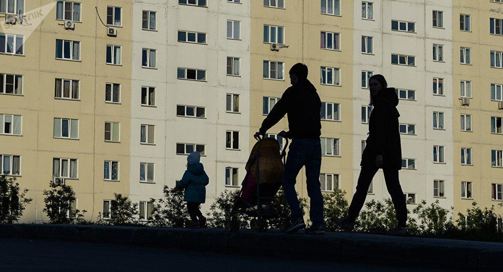 Молодая семья у многоэтажного дома. Архивное фото