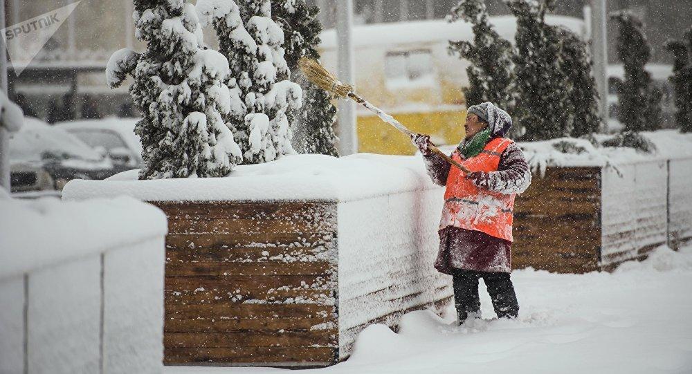 Сотрудница МП Тазалык убирает снег на одной из улиц Бишкека. Архивное фото