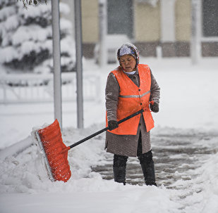 Сотрудница МП Тазалык убирает снег на одном из улиц Бишкека. Архивное фото