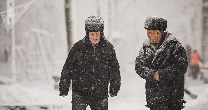 Мужчина идут по улице во время обильного снегопада в Бишкеке. Архивное фото