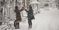 Пара на одном из улиц Бишкека во время обильного снегопада. Архивное фото