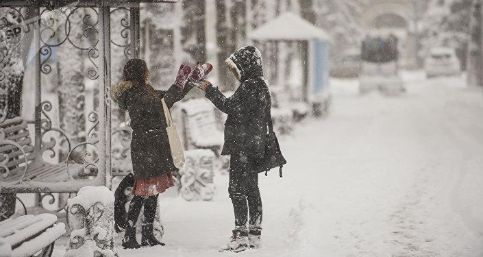 Пара на одной из улиц Бишкека во время снегопада. Архивное фото