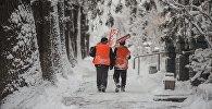 Сотрудники МП Тазалык с лопатами идут по улице во время снегопада в Бишкеке. Архивное фото