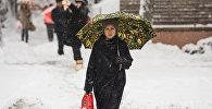 Женщина с зонтом идет по улице во время обильного снегопада в Бишкеке. Архивное фото