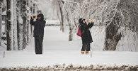 Люди фотографируют на телефон во время обильного снегопада в Бишкеке